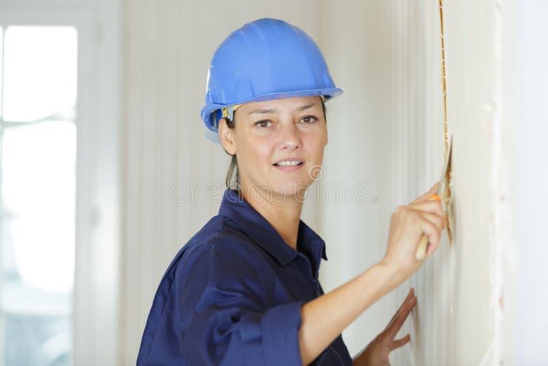 去除墙纸的妇女与刮板 免版税库存照片