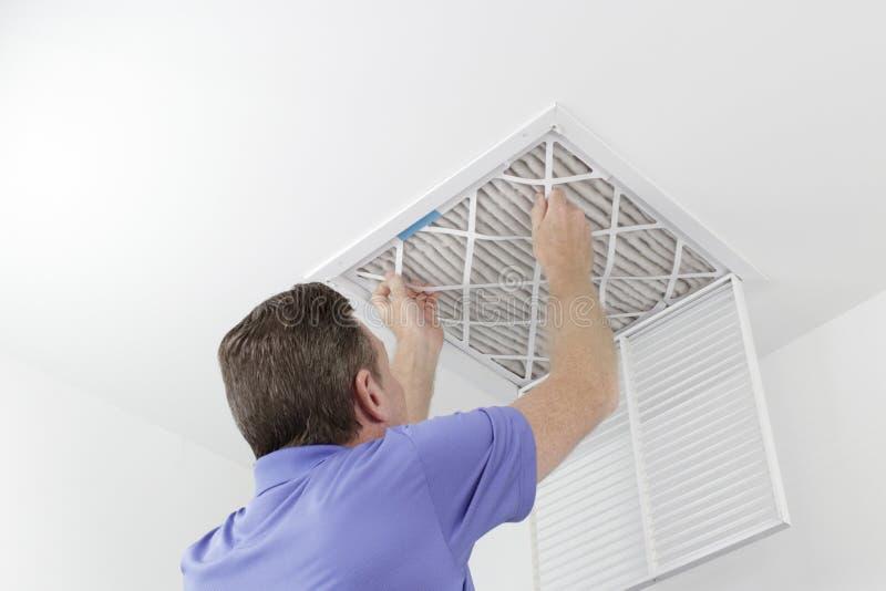 去除天花板空气过滤器的人 免版税库存图片
