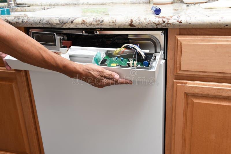 去除控制板的装置安装工的特写镜头对一台残破的洗碗机 免版税图库摄影