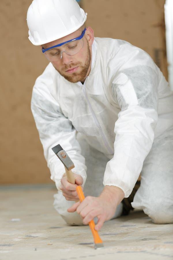 去除瓦片的年轻建造者使用锤子和凿子 免版税库存图片