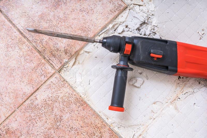去除老瓦片 手提凿岩机-在地板上的钻井的爆破锤子 免版税库存照片