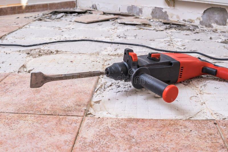去除老瓦片 手提凿岩机-在地板上的钻井的爆破锤子 库存照片