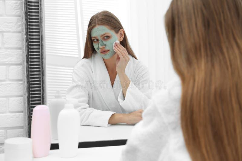 去除自创黏土面具的美女从她的面孔在镜子 免版税库存照片
