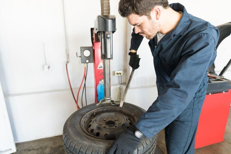去除轮胎的安装工从在机器的外缘在车库 库存照片