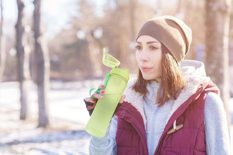 参与一种锻炼体育女孩的画象在的冬天户外运动调遣 饮料浇灌止干渴 库存照片