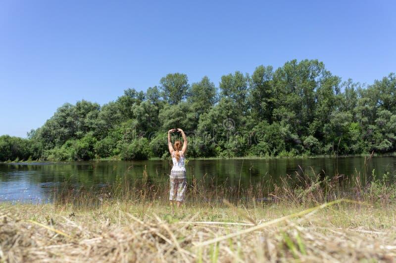 参与在河的河岸的瑜伽体操红发女孩树背景的在一夏天好日子 免版税库存图片