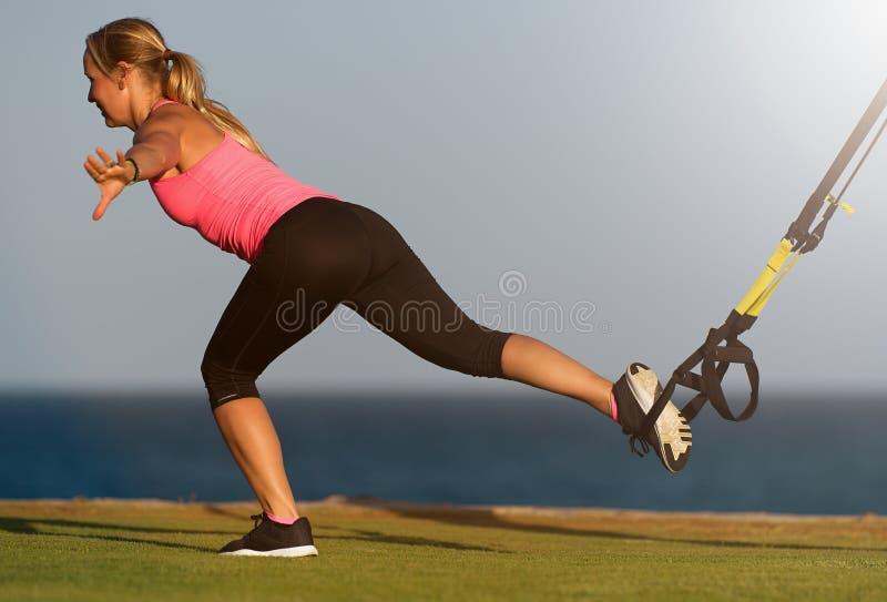 参与在海滩的早晨运动健身年轻女人在日出,刺后面trx期间 库存图片