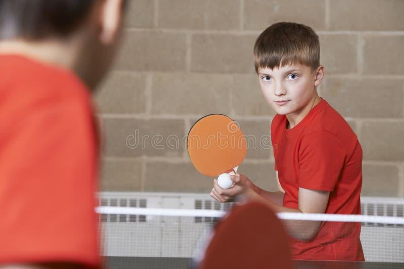 参加在学校健身房的两个男孩乒乓球比赛 免版税库存图片