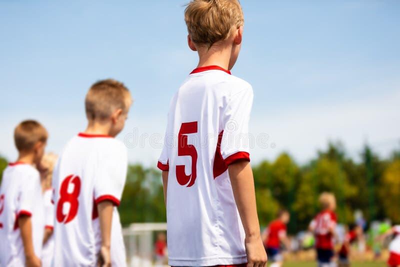 参加在橄榄球场的男孩足球足球赛 踢球的孩子 免版税图库摄影