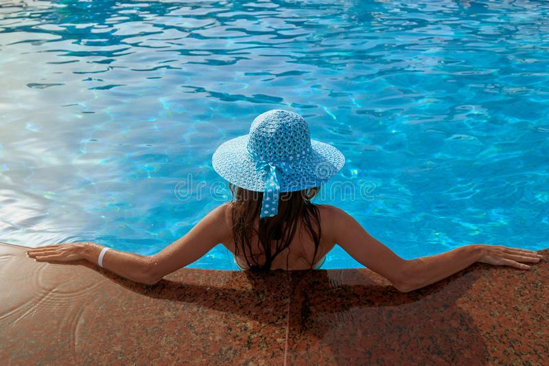 参加在游泳池夏天边缘的帽子的美丽的妇女户外,概念放松并且旅行 库存图片