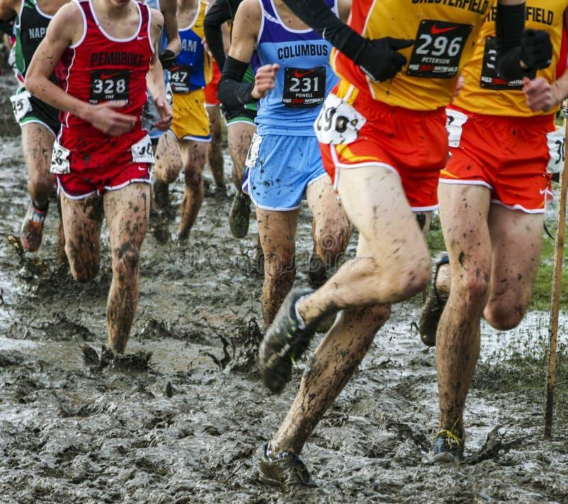 参加比赛的男孩通过泥 库存图片