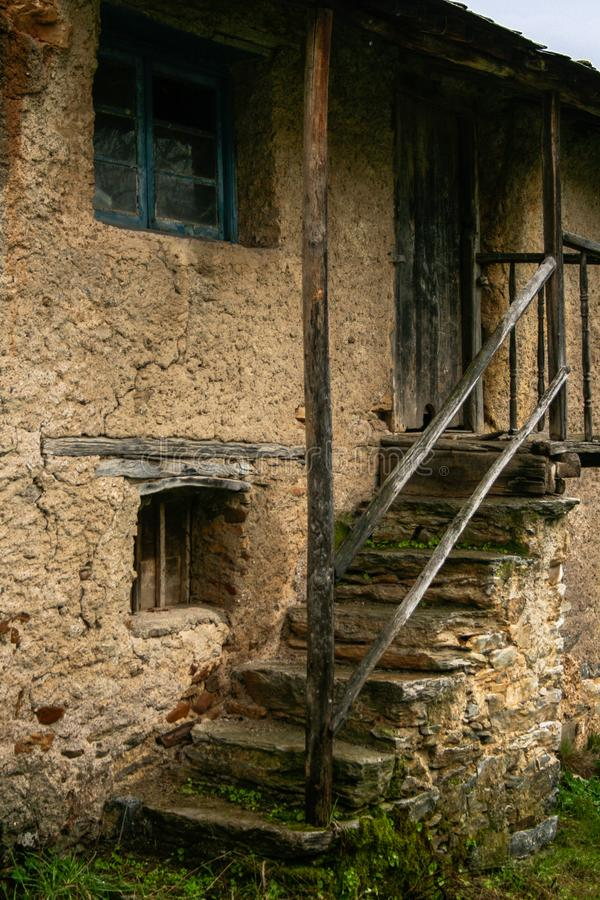 参差不齐的石台阶在有草的一个老房子里和青苔和木门框 免版税库存图片