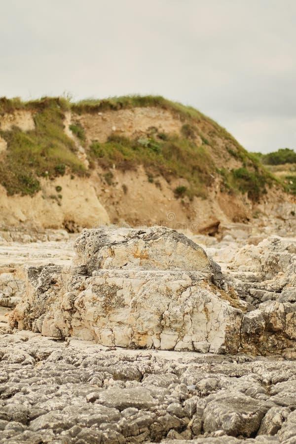 参差不齐的被腐蚀的岩石达尔马希亚岸:有疏散干燥植被的锋利的砌石护面淡光的海在一个光彩的晴朗的夏天d 免版税库存照片