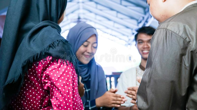 参观他们的家庭或朋友家的回教夫妇模糊的画象,当震动手和拥抱在eid穆巴拉克庆祝时 免版税库存照片