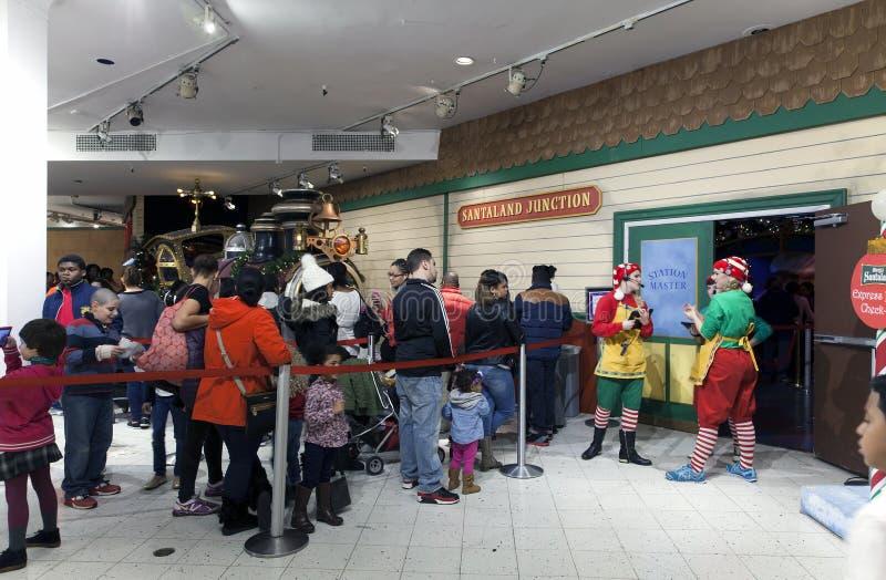 参观在梅西百货公司里面的圣诞老人的线的人们NYC的 图库摄影