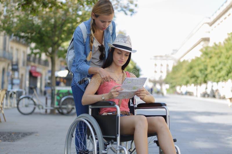参观外国城市一的两个朋友坐在轮椅 免版税库存照片