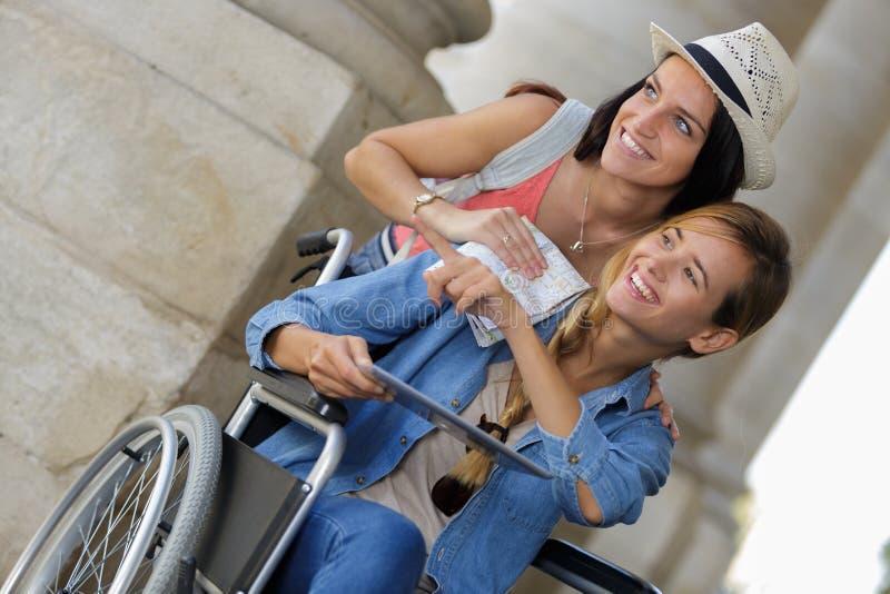 参观外国城市一的两个朋友坐在轮椅 库存图片