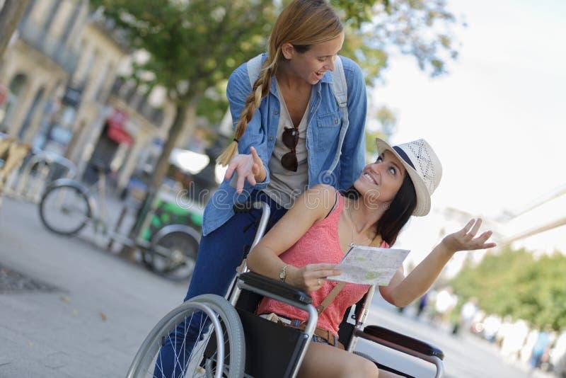 参观外国城市一的两个朋友坐在轮椅 库存照片