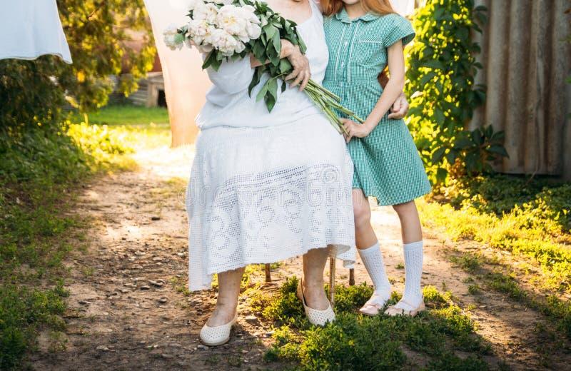 参观祖母 祖母,坐和拥抱她的孙女,女孩和拿着的年长妇女花花束在的 库存照片