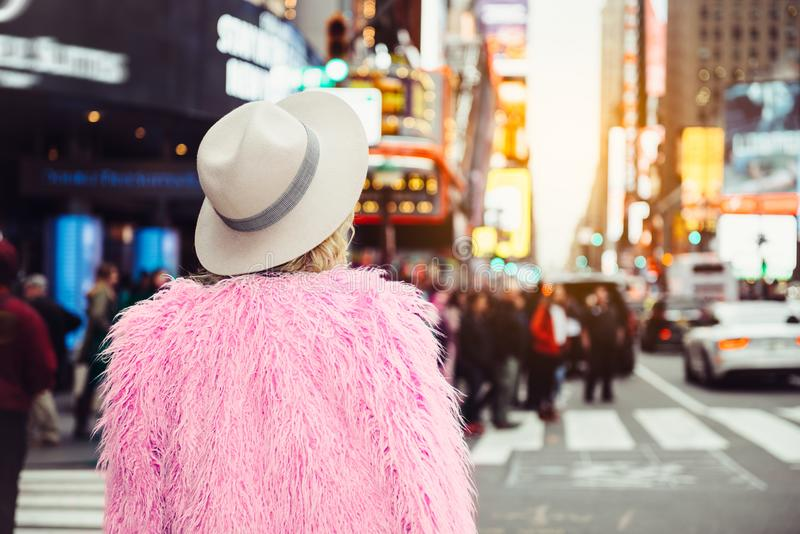 参观纽约时间` s方形的佩带的时髦的街道样式成套装备的时兴的旅游妇女 图库摄影