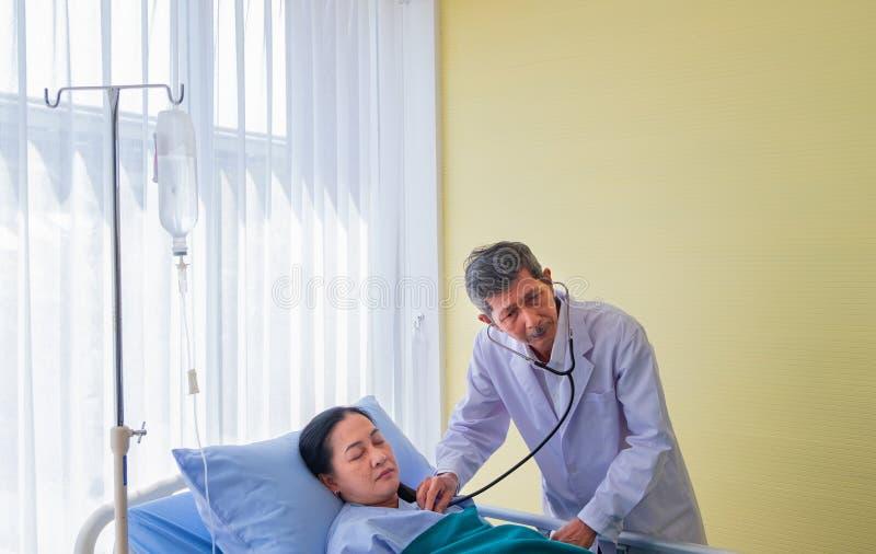 参观资深亚裔男性的医生和检查病区的中年女性患者 在屋子医院里 免版税库存照片