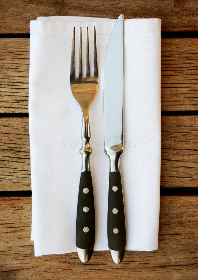 叉子、刀子和餐巾在桌上 免版税库存照片
