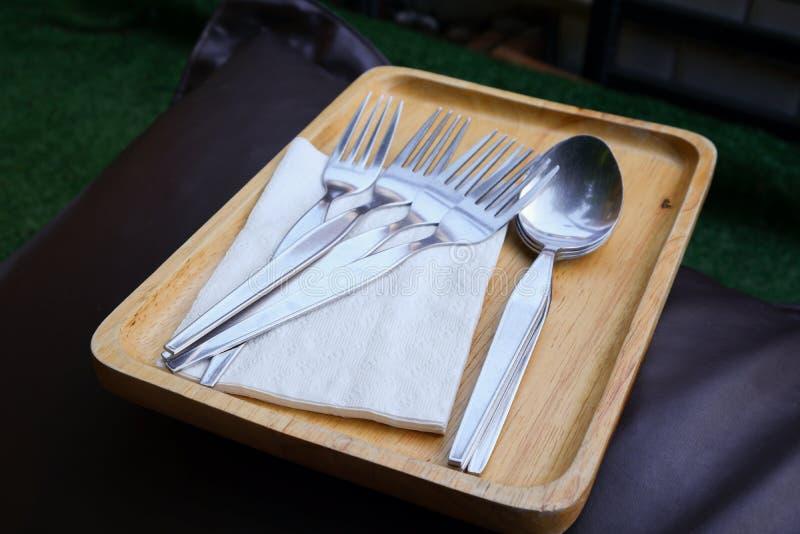 叉子、匙子和薄纸在木盘子 库存图片