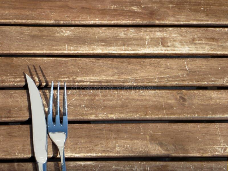 叉子和刀子在木表上 免版税库存图片
