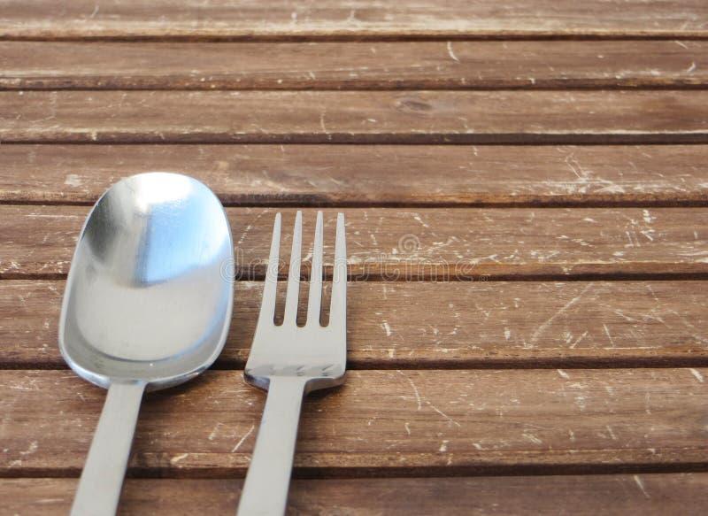 叉子和匙子在一张木桌上与银色蓝色绿松石反射 库存照片