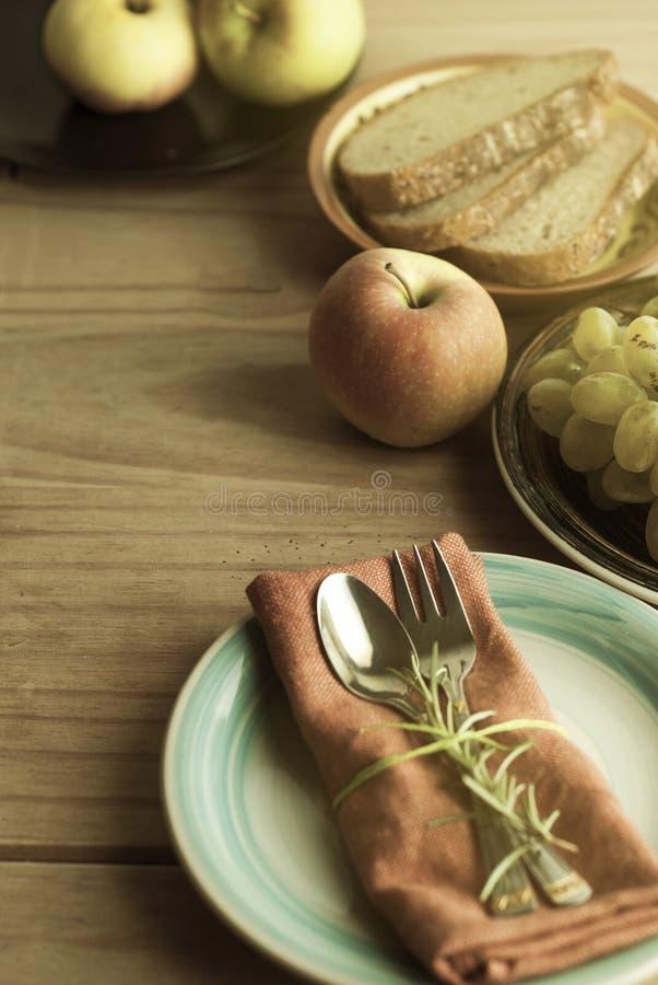叉子和匙子在餐巾,与迷迭香的枝杈 果子和面包在背景 健康的食物 背景土气木 食物 库存照片