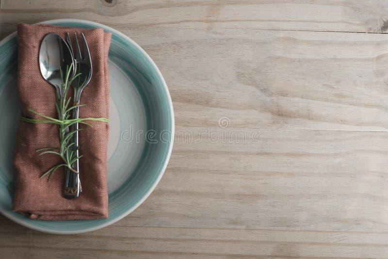 叉子和匙子在餐巾,与迷迭香的枝杈 背景土气木 食物教育 健康的食物 复制空间 免版税库存图片