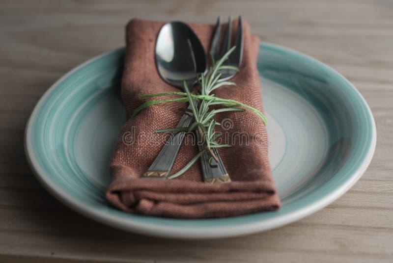 叉子和匙子在餐巾,与迷迭香的枝杈 背景土气木 食物教育 健康的食物 复制空间 免版税图库摄影
