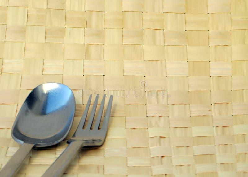 叉子和匙子有银色蓝色绿松石反射的在韧皮竹子背景 库存照片