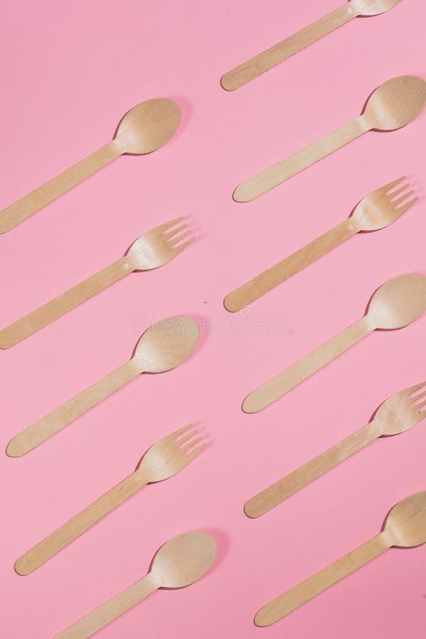 叉子和匙子说谎的平行在桃红色桌上 免版税库存照片