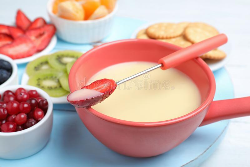 叉子用草莓蘸入白色巧克力涮制菜肴和陶瓷罐 库存图片