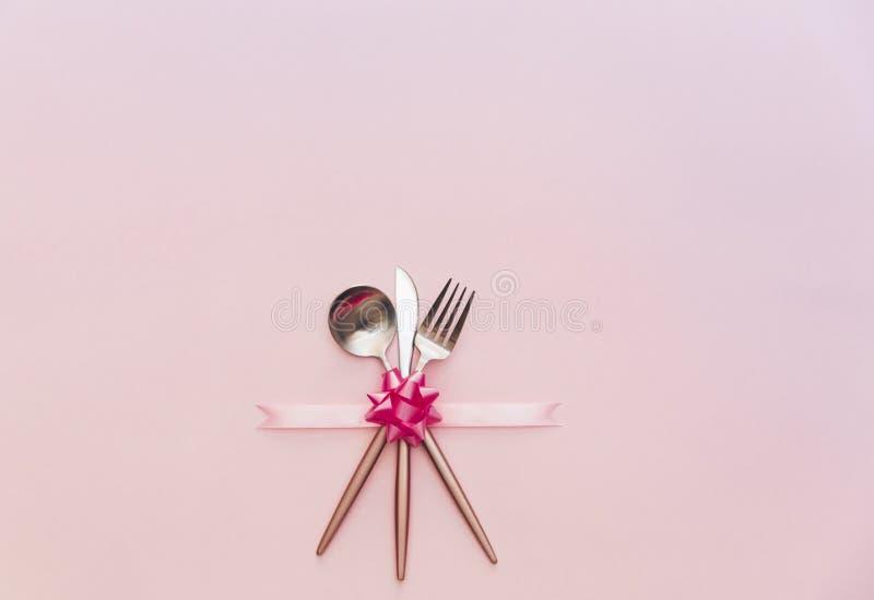 叉子,刀子,匙子,银器有在承办宴席的桃红色背景, 库存图片