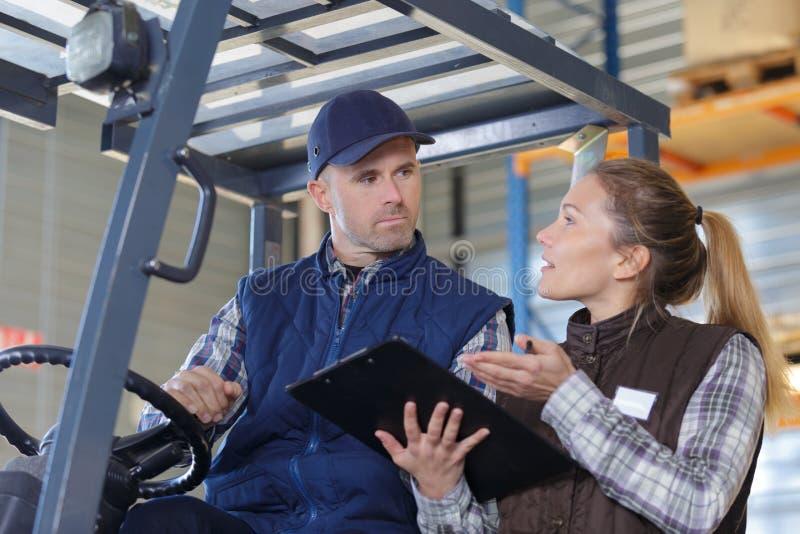 叉架起货车司机谈论清单与经理在仓库 免版税库存照片