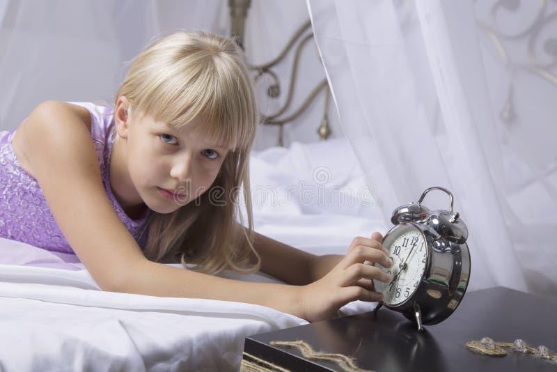 及早唤醒 停止在一张床上的醒一个睡着的女孩闹钟早晨 库存图片