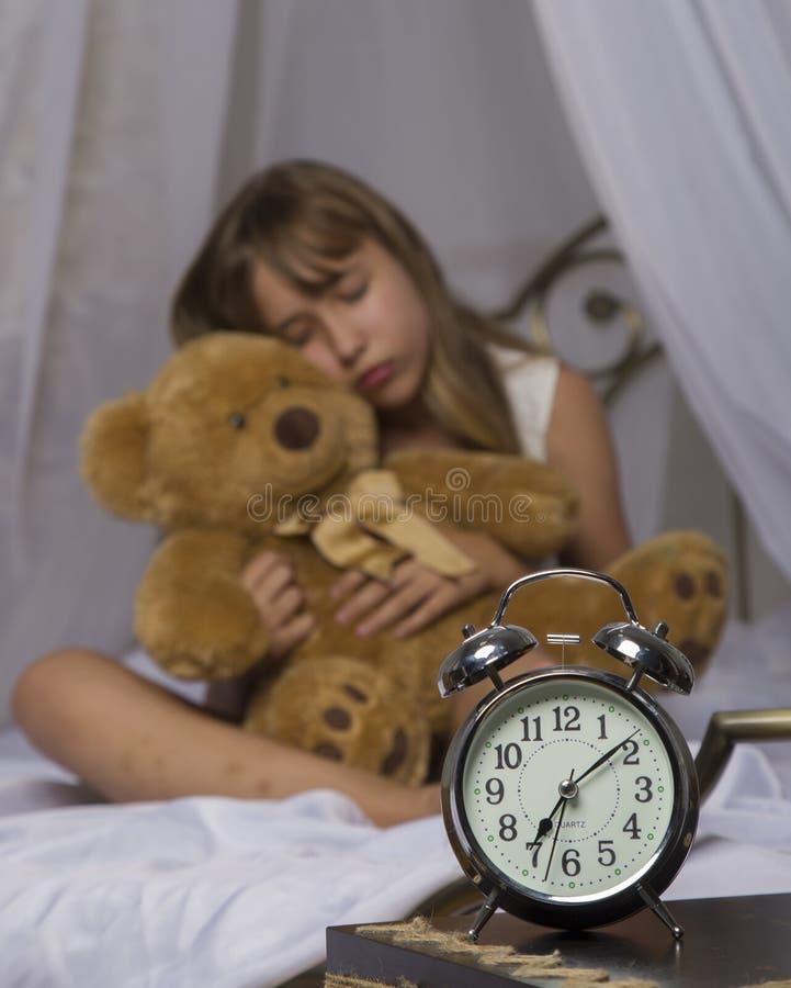 及早唤醒 站立在床头柜上的闹钟 拿着玩具熊在a的床上的醒一个睡着的女孩 库存图片