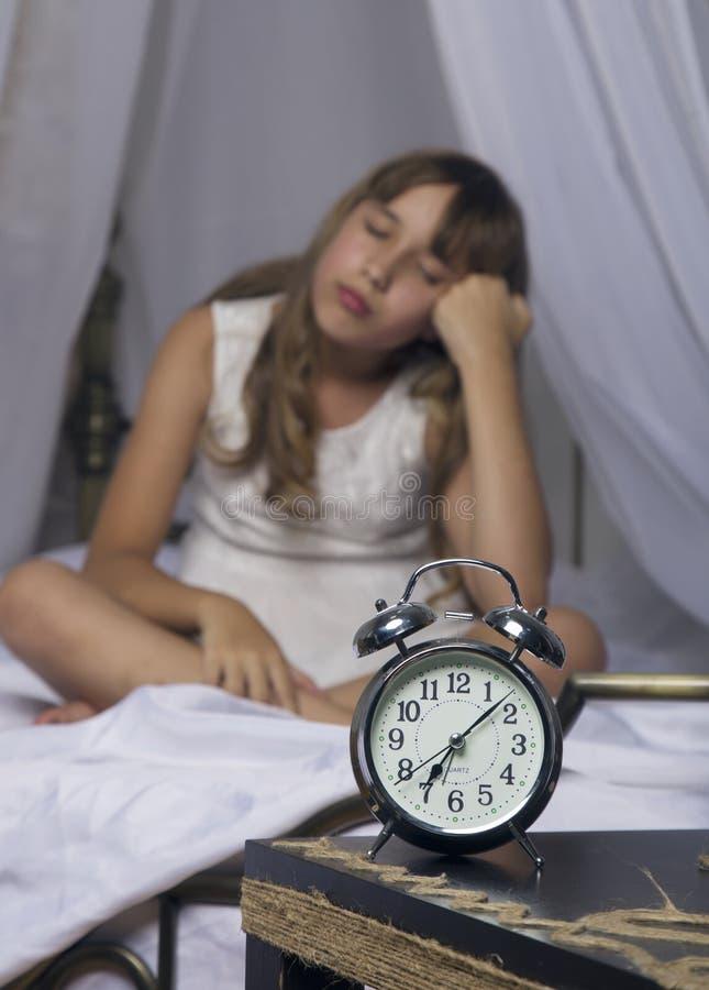 及早唤醒 站立在床头柜上的闹钟 醒一个睡着的女孩在背景的床上 库存照片