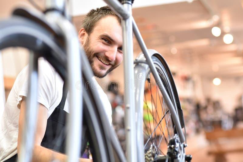 友好和能干自行车技工在车间修理自行车 免版税库存照片