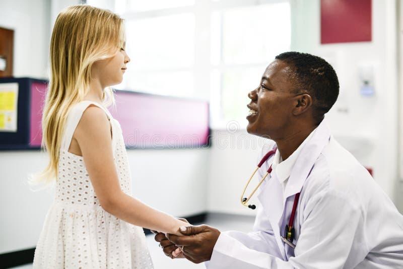 友好的儿科医生谈话与她的小患者 图库摄影