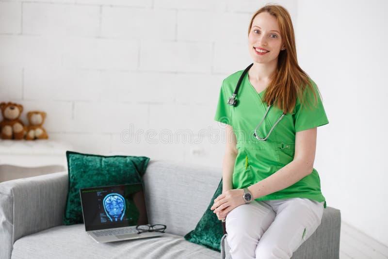 友好的医生神经学家画象绿色制服的 有X线体层照相术图象的膝上型计算机 儿童` s家医生概念 免版税库存图片