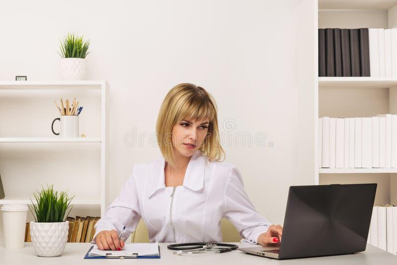 友好的女性医生工作在她的书桌在办公室 免版税库存照片