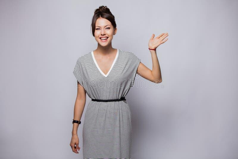 友好的妇女对新的邻居说喂 挥动用被举的手,问候的迷人的年轻感情妇女画象或 免版税库存照片