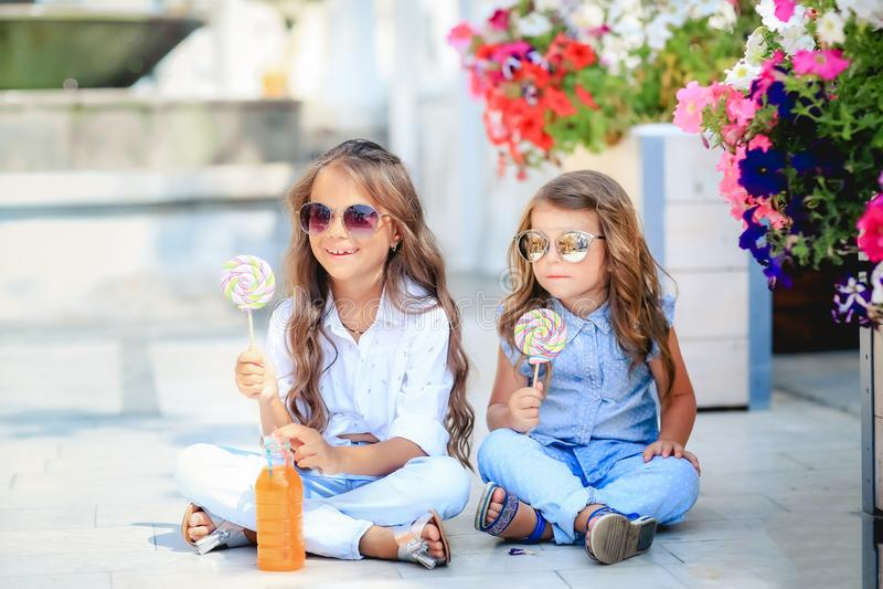 友好的孩子女孩和乐趣情感母亲饮用的莓果圆滑的人汁一起在街道咖啡馆和看在其中每一 免版税图库摄影