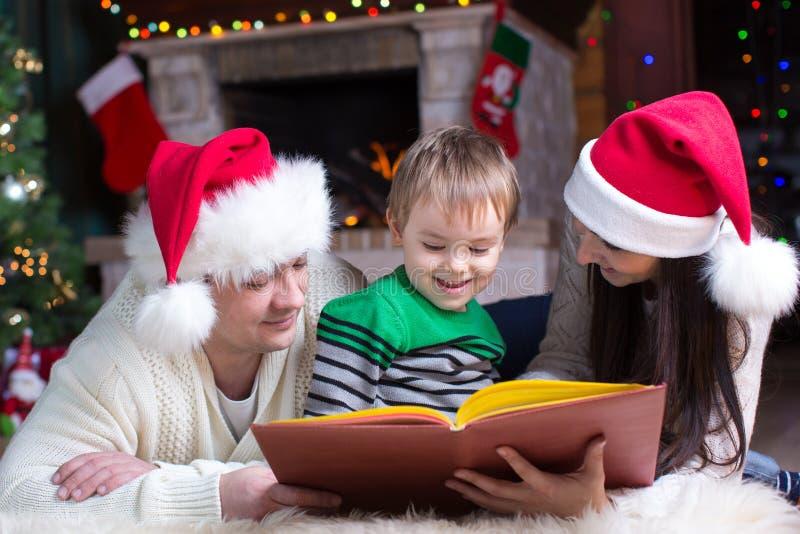 友好的家庭阅读书在圣诞节晚上 免版税库存照片