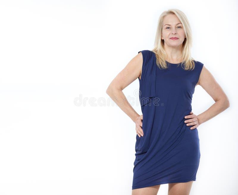 友好的微笑的中年妇女我在白色背景隔绝的蓝色礼服的 免版税图库摄影