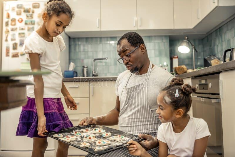 友好的快乐的看他们的曲奇饼的父亲和他的女孩 库存图片