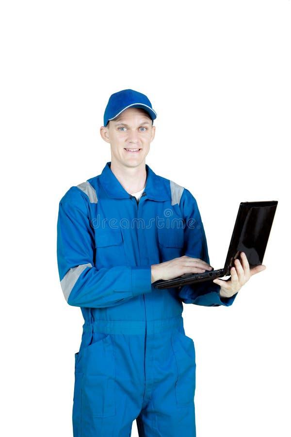 友好的技工与在演播室的一台膝上型计算机一起使用 免版税库存图片